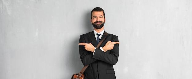 Homme d'affaires avec barbe pointant vers les latéraux ayant des doutes