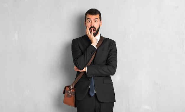 Homme d'affaires avec barbe surpris et choqué en regardant à droite