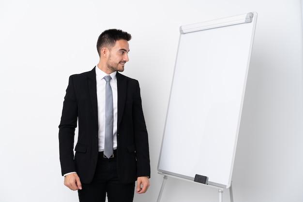 Homme d'affaires avec barbe avec tableau blanc sur mur isolé