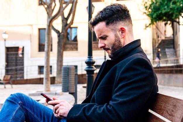 Homme d'affaires à la barbe taillée assis sur un banc de la ville. en utilisant son téléphone portable.