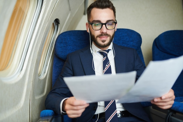 Homme d'affaires barbu en avion