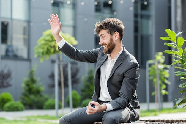 Homme d'affaires barbu caucasien fumant du cannabis à l'extérieur assis sur un banc de parc de la ville sur fond de rue urbaine. employé de sexe masculin employé de bureau en costume soulage le stress d'une marijuana à l'extérieur