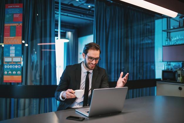 Homme d'affaires barbu caucasien optimiste attrayant en costume et avec des lunettes assis dans la cuisine de l'entreprise, boire du café et avoir un appel vidéo sur ordinateur portable.