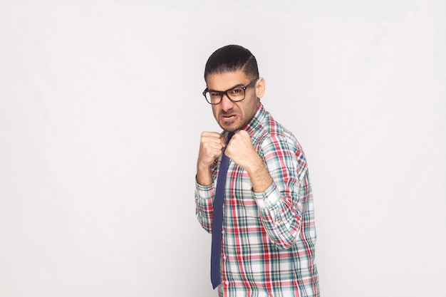 Homme d'affaires barbu en colère en chemise à carreaux colorée, cravate bleue et lunettes noires debout et regardant la caméra avec un visage et un poing agressifs. tourné en studio intérieur, isolé sur fond gris clair