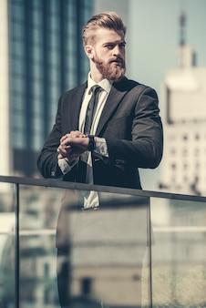 Homme d'affaires barbu en costume classique cherche loin.