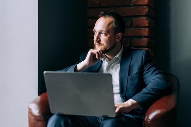 Homme d'affaires barbu est assis pensif avec un ordinateur portable dans un intérieur moderne.