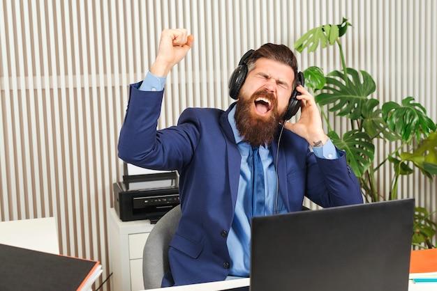 Homme d'affaires barbu excité dans les écouteurs sur le lieu de travail. homme prospère travaillant au bureau.