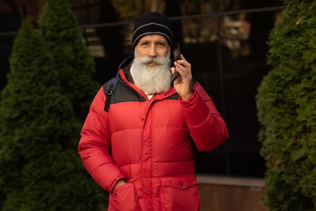 Homme d'affaires barbu mature à l'aide de téléphone dans la ville à l'extérieur