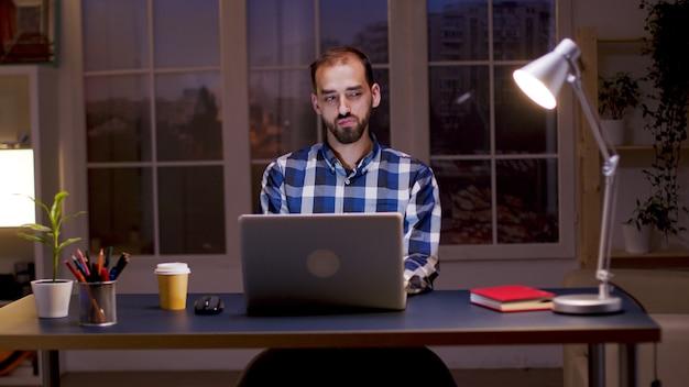 Homme d'affaires barbu portant une chemise et prenant une gorgée de café tout en travaillant à domicile la nuit.