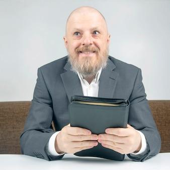 Homme d'affaires barbu prospère priant et étudiant de la bible