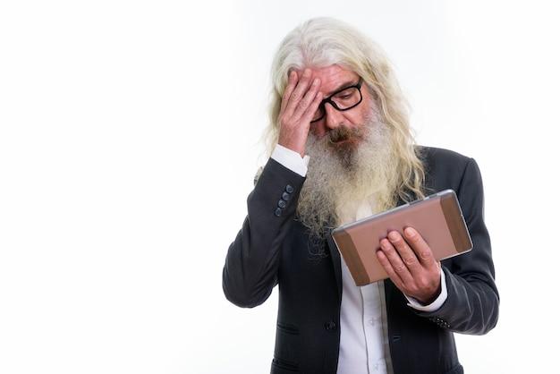 Homme d'affaires barbu senior à l'aide de tablette numérique