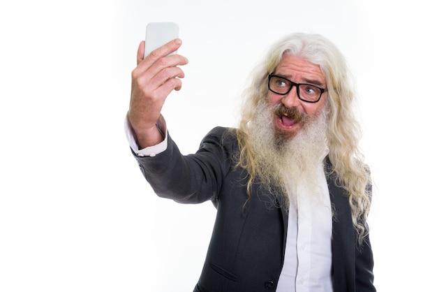 Homme d'affaires barbu senior prenant une photo de selfie