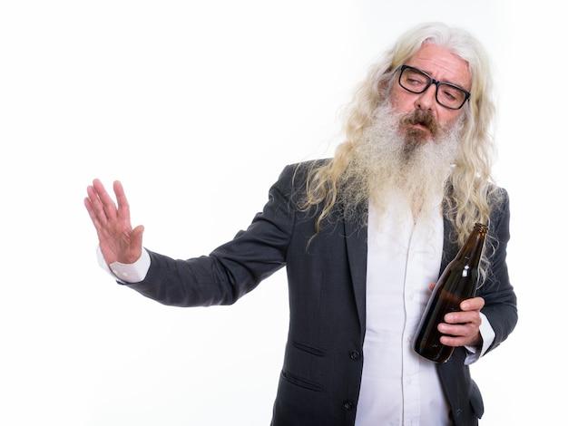 Homme d'affaires barbu senior tenant une bouteille de bière