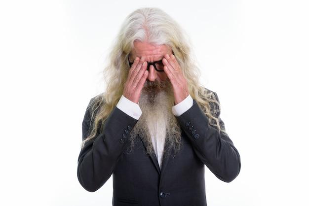 Homme d'affaires barbu senior triste ayant des maux de tête