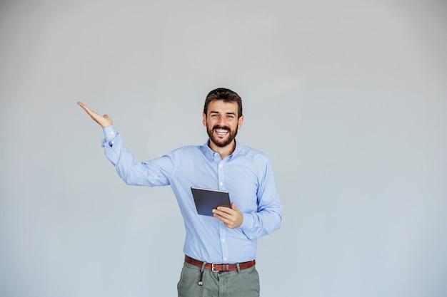 Homme d'affaires barbu souriant debout et tenant la tablette. il fait des gestes comme s'il tenait quelque chose.