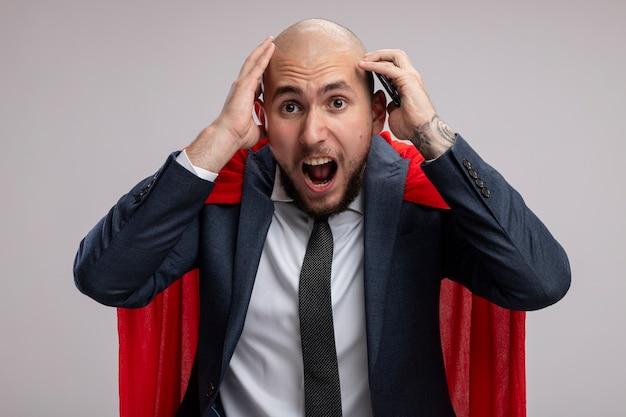 Homme d'affaires barbu de super héros en cape rouge à l'aide de smartphone criant d'être frustré debout sur un mur blanc