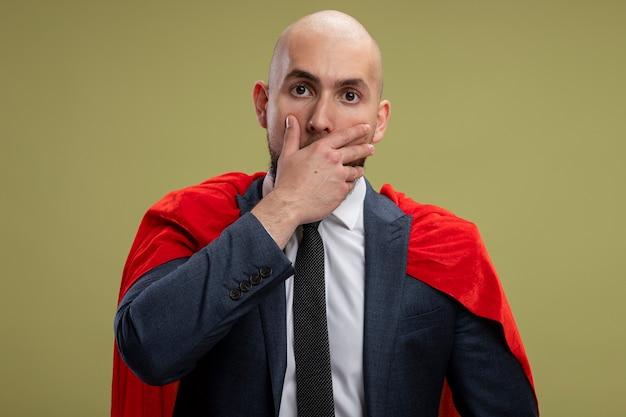 Homme D'affaires Barbu Super Héros En Cape Rouge Beiing Choqué Couvrant La Bouche Avec La Main Debout Sur Un Mur Vert Clair Photo gratuit