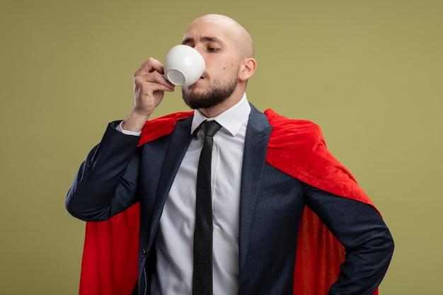 Homme d'affaires barbu super héros en cape rouge, boire du café à la confiance debout sur un mur vert clair