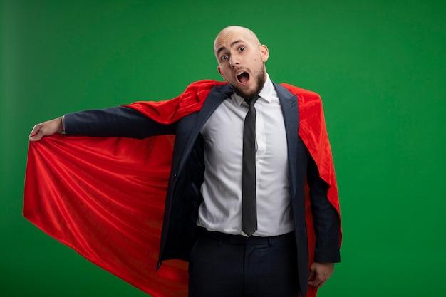 Homme d'affaires barbu super héros en cape rouge confus levant la main sur le mur vert