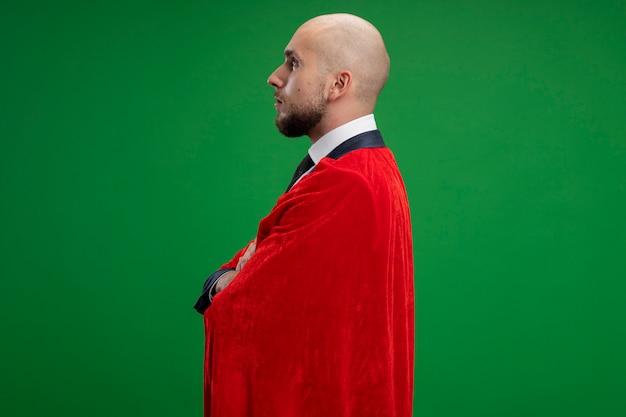 Homme d'affaires barbu super héros en cape rouge debout sur le côté avec un visage sérieux sur mur vert