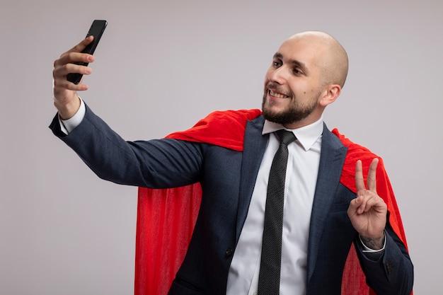 Homme d'affaires barbu super héros en cape rouge faisant selfie à l'aide de smartphone souriant montrant v-sign debout sur un mur blanc