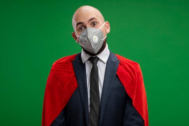 Homme d'affaires barbu super héros en cape rouge et masque facial de protection confus debout sur mur vert
