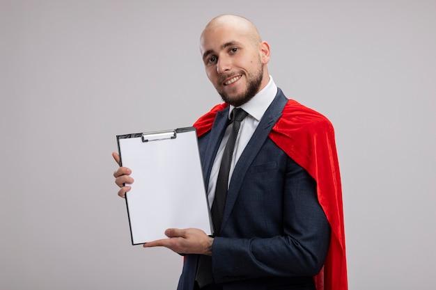 Homme d'affaires barbu de super héros en cape rouge montrant le presse-papiers avec des pages blanches avec le sourire sur le visage debout sur un mur blanc