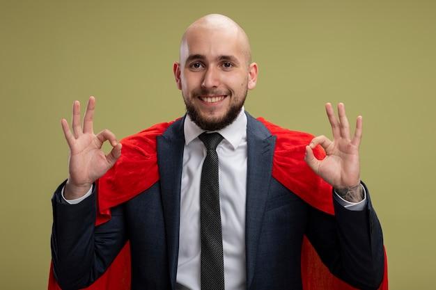 Homme d'affaires barbu super héros en cape rouge à la recherche de sourire joyeusement montrant signe ok debout sur un mur vert clair