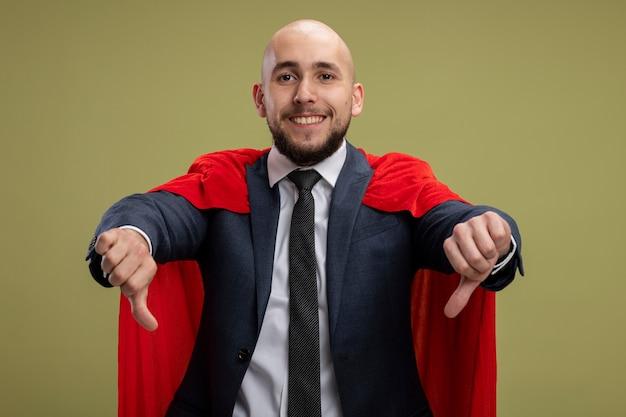 Homme d'affaires barbu super héros en cape rouge à la recherche de sourire montrant les pouces vers le bas debout sur un mur vert clair