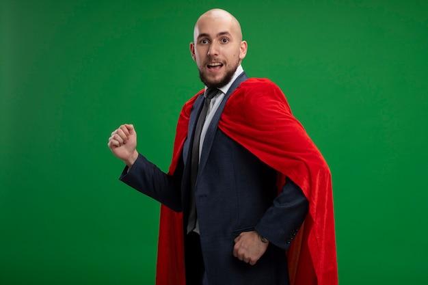 Homme d'affaires barbu super héros en cape rouge se précipiter avec les poings fermés prêt à aider debout sur le mur vert