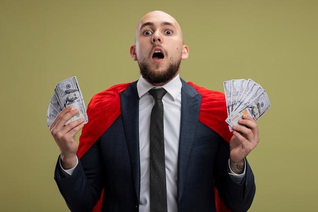 Homme d'affaires barbu super héros en cape rouge tenant de l'argent surpris et étonné debout sur un mur vert clair