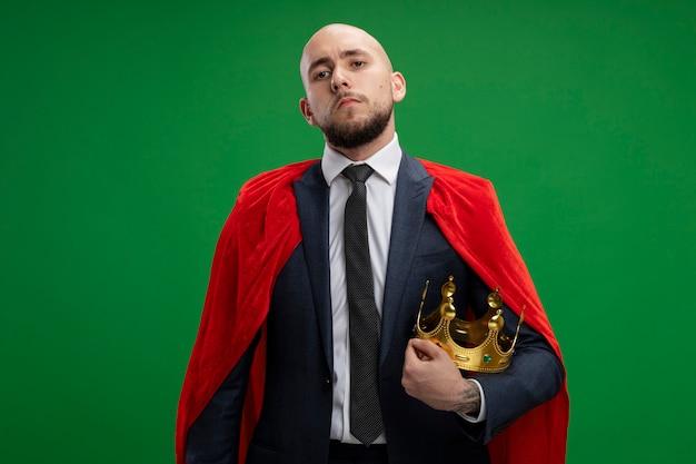 Homme d'affaires barbu super héros en cape rouge tenant la couronne à la confiance debout sur le mur vert