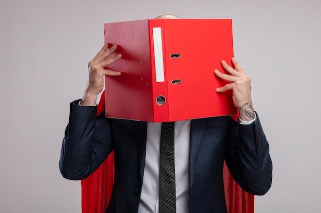 Homme d'affaires barbu super héros en cape rouge tenant un dossier ouvert couvrant son visage derrière lui debout sur un mur blanc