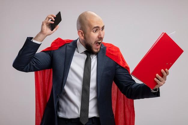 Homme d'affaires barbu super héros en cape rouge tenant un dossier rouge et un smartphone criant avec une expression agressive debout sur un mur blanc