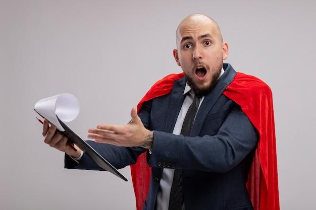 Homme d'affaires barbu de super héros en cape rouge tenant le presse-papiers avec des pages vierges pointant avec la main sur eux d'être surpris et surpris debout sur un mur blanc