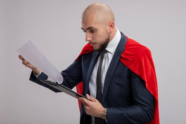 Homme d'affaires barbu super héros en cape rouge tenant le presse-papiers avec des pages vierges les regardant être confus debout sur un mur blanc