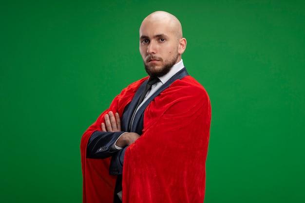 Homme d'affaires barbu super héros en cape rouge avec un visage sérieux avec les bras croisés sur la poitrine debout sur le mur vert