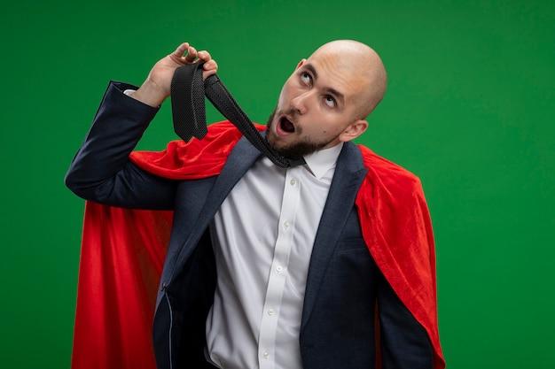 Homme d'affaires barbu super-héros dérangé en cape rouge tenant sa cravate se pendre debout sur un mur vert