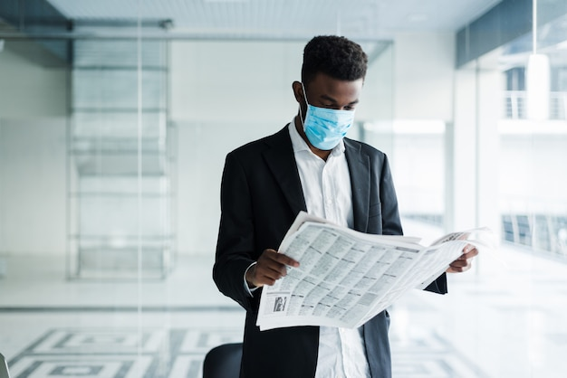 Homme d'affaires beau africain en masque médical lisant le journal à l'immeuble de bureaux