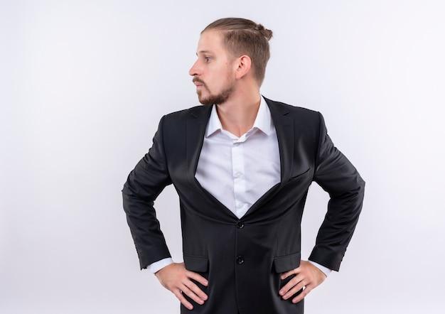 Homme d'affaires beau gêné portant costume à côté debout sur fond blanc