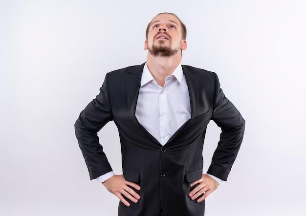 Homme d'affaires beau gêné portant costume à la recherche debout sur fond blanc