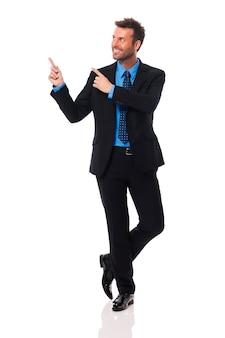 Homme d'affaires beau et souriant, pointant sur l'espace de copie