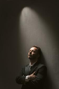 Homme d'affaires bien pensé se tient les bras croisés. bel homme bien habillé en vetu noir seul sur fond gris foncé