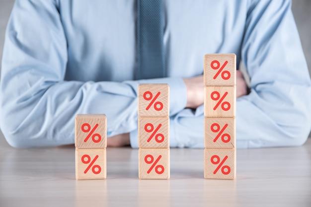 Homme d'affaires avec des blocs de cube en bois montrant l'icône de symbole de pourcentage