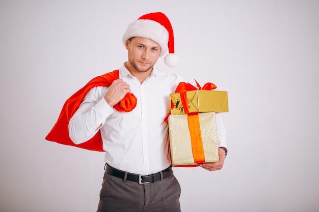 Homme d'affaires en bonnet de noel tenant le cadeau de noël isolé