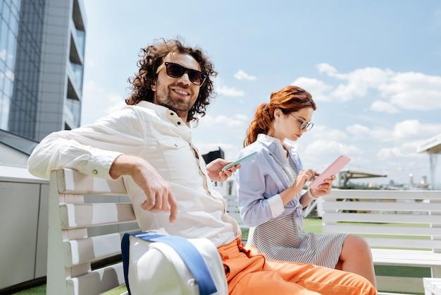 Homme d'affaires bouclé. bel homme d'affaires frisé se détendre sur la terrasse d'été avec sa jeune petite amie attrayante
