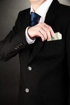 Homme d'affaires cachant de l'argent dans la poche sur fond noir