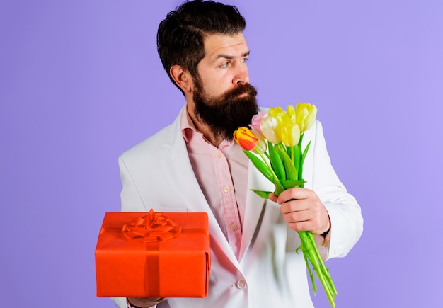 Homme d'affaires avec cadeau et bouquet. homme romantique avec tulipes et présent. saint valentin, fête des femmes, anniversaire.