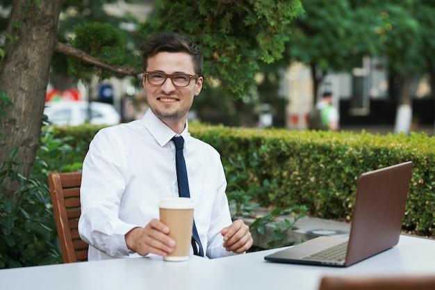 Homme d'affaires avec café avec ordinateur portable à la table