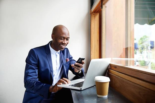 Homme affaires, café, regarder, ordinateur portable, smartphone